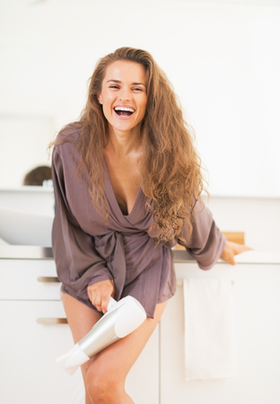 Smiling long hair woman with blow dryer in bathroom photo