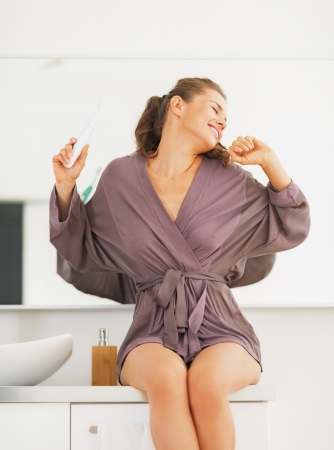 Young woman with toothbrush stretching after sleep in\ bathroom