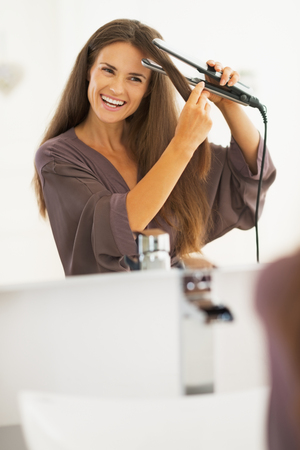 straightener: Smiling young woman straightening hair with straightener