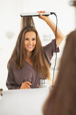 straightener: Portrait of happy woman straightening hair with straightener Stock Photo