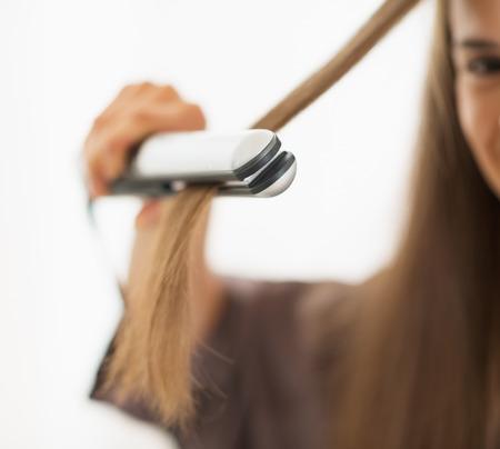 straightener: Closeup on woman straightening hair with straightener