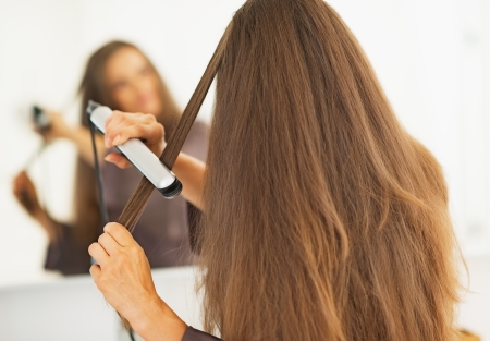straightener: Woman straightening hair with straightener . rear view Stock Photo