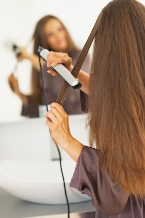 anonym: Woman straightening hair with straightener . rear view Stock Photo