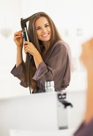 curling: Smiling woman curling hair with straightener