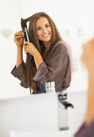 straightener: Smiling woman curling hair with straightener