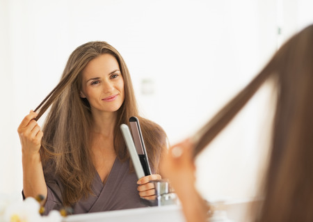 capelli lisci: Felice giovane donna che controlla i capelli dopo il raddrizzamento