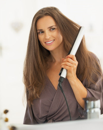 straightener: Young woman curling hair with straightener