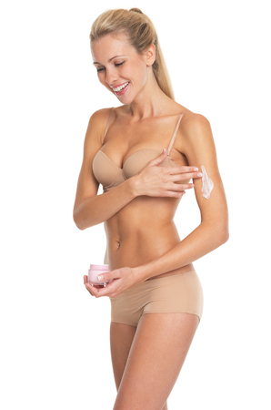 Smiling young woman in lingerie applying creme on arm photo