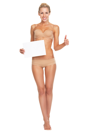 Full length portrait of happy young woman in lingerie showing blank paper sheet and thumbs up photo