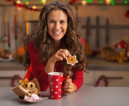 Happy young woman in red dress having snack in christmas decorated kitchen photo