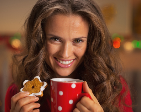 Portrait of smiling young woman with cup of hot chocolate and christmas cookie photo