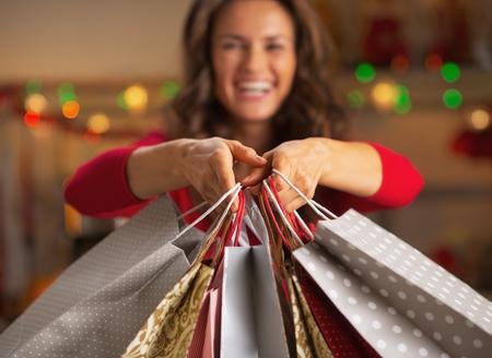 prázdniny: Detailním na vánoční nákupními taškami v ruce usmívající se mladé ženy Reklamní fotografie