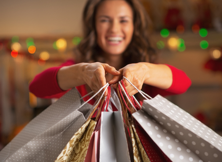 vacaciones: Primer en Navidad bolsas de la compra en la mano de la mujer sonriente joven