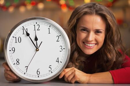 Happy young woman showing clock in christmas decorated kitchen photo