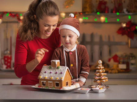 Happy mother and baby decorating christmas cookie house in kitchen photo