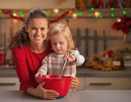 Baby helping mother make christmas cookies photo