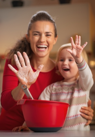 Closeup on mother and baby hands smeared in flour photo
