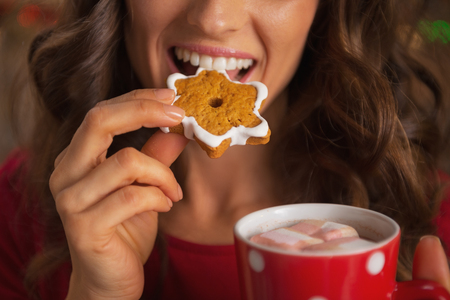 Closeup on happy young woman eating christmas cookie photo