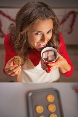 Happy young housewife drinking hot chocolate and eating cookie from pan with christmas cookies photo