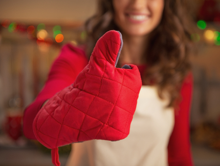 Closeup on young housewife in kitchen gloves showing thumbs up in christmas decorated kitchen Stock Photo - 23532980