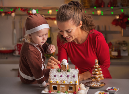Happy mother and baby decorating christmas cookie house photo