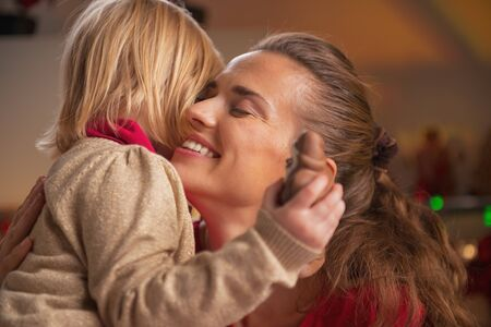 Portrait of baby hugging mother in christmas decorated kitchen photo