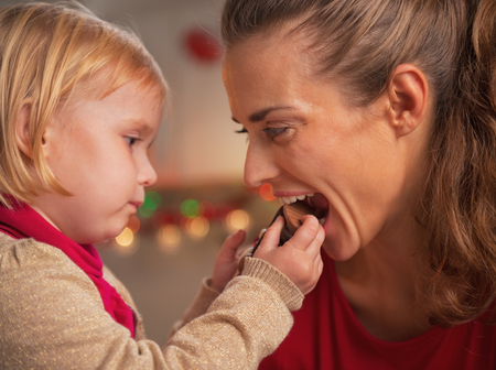 Baby giving mother bite of chocolate santa