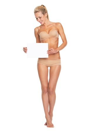 Full length portrait of happy young woman in lingerie looking on blank paper sheet photo