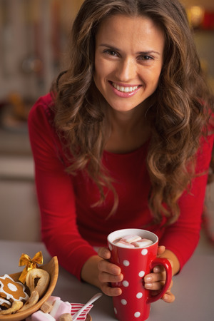 Happy young woman in red dress having christmas snack photo