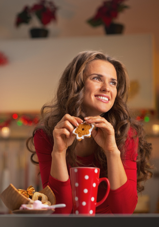 Thoughtful young woman in red dress having snack in christmas decorated kitchen photo