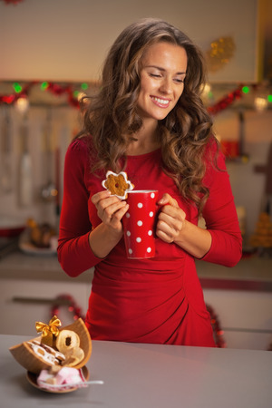 Thoughtful young woman in red dress with cup of hot chocolate and christmas cookie photo