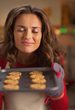 baking christmas cookies: Happy young housewife enjoying smell of christmas cookies on pan