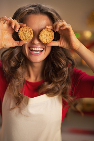 Happy young housewife holding christmas cookie in front of eyes