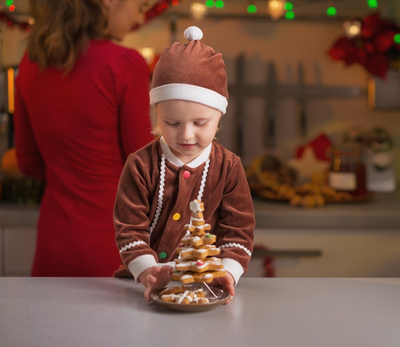 Baby helping mother making christmas preparations on kitchen photo