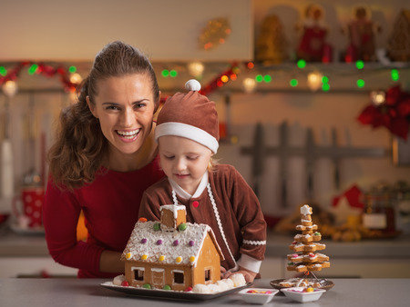 Smiling mother and baby decorating christmas cookie house in kitchen photo