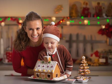 galletas de navidad: Sonriendo madre y el bebé decorar la casa de galletas de Navidad en la cocina