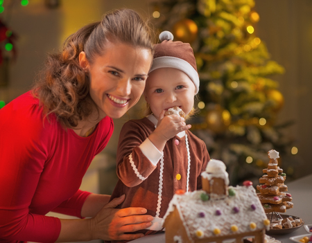 Portrait of happy mother and baby eating cookie in christmas decorated kitchen photo