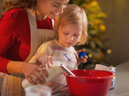 Mother and baby making christmas cookies in kitchen Stock Photo - 23533202