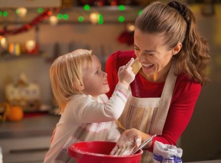 mujeres cocinando: Bebé tratando de difamar a las madres nariz con harina al hacer galletas de Navidad Foto de archivo