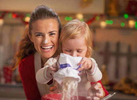 Portrait of happy mother and baby making christmas cookies Stock Photo - 23533204