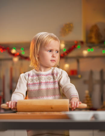 Portrait of baby rolling pin dough in christmas decorated kitchen Stock Photo - 23533205