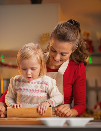 Mother and baby rolling pin dough in christmas decorated kitchen Stock Photo - 23533206
