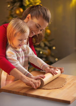 Smiling mother and baby rolling pin dough in christmas decorated kitchen Stock Photo - 23533207