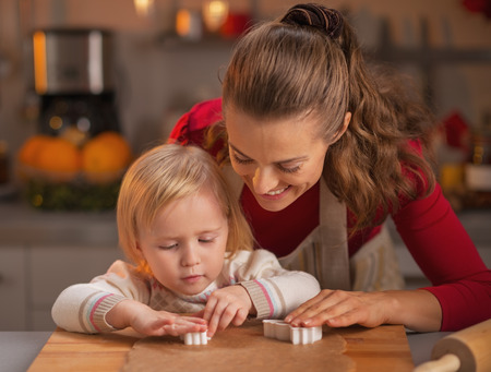 Happy mother and baby cutting christmas cookies from dough Stock Photo - 23533208
