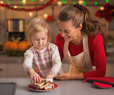 Baby taking homemade christmas cookies from plate Stock Photo - 23533209