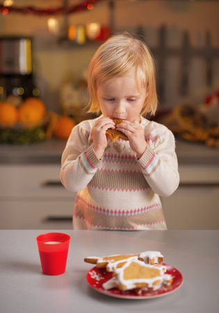 Baby tasting homemade christmas cookies in christmas decorated kitchen Stock Photo - 23533210
