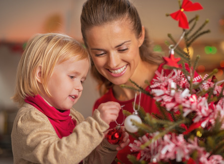Baby helping mother decorate christmas tree Stock Photo - 23533212