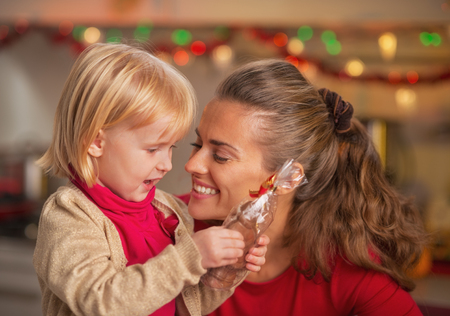 Portrait of happy mother and baby with chocolate santa Stock Photo - 23533213