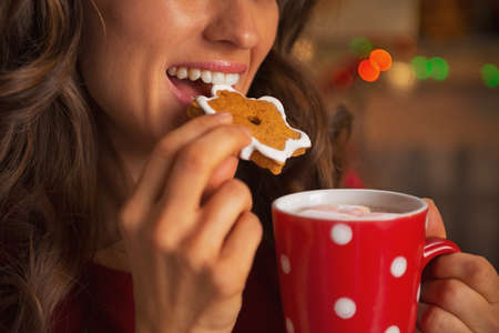 Closeup on young woman eating christmas cookie photo