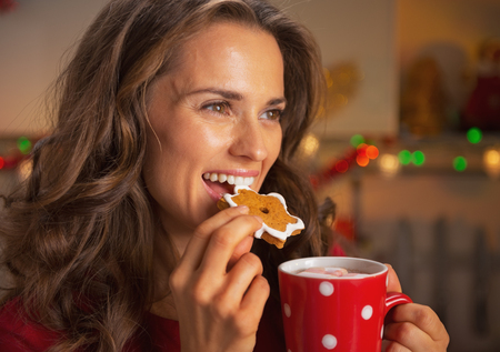 Happy young woman eating christmas cookie photo